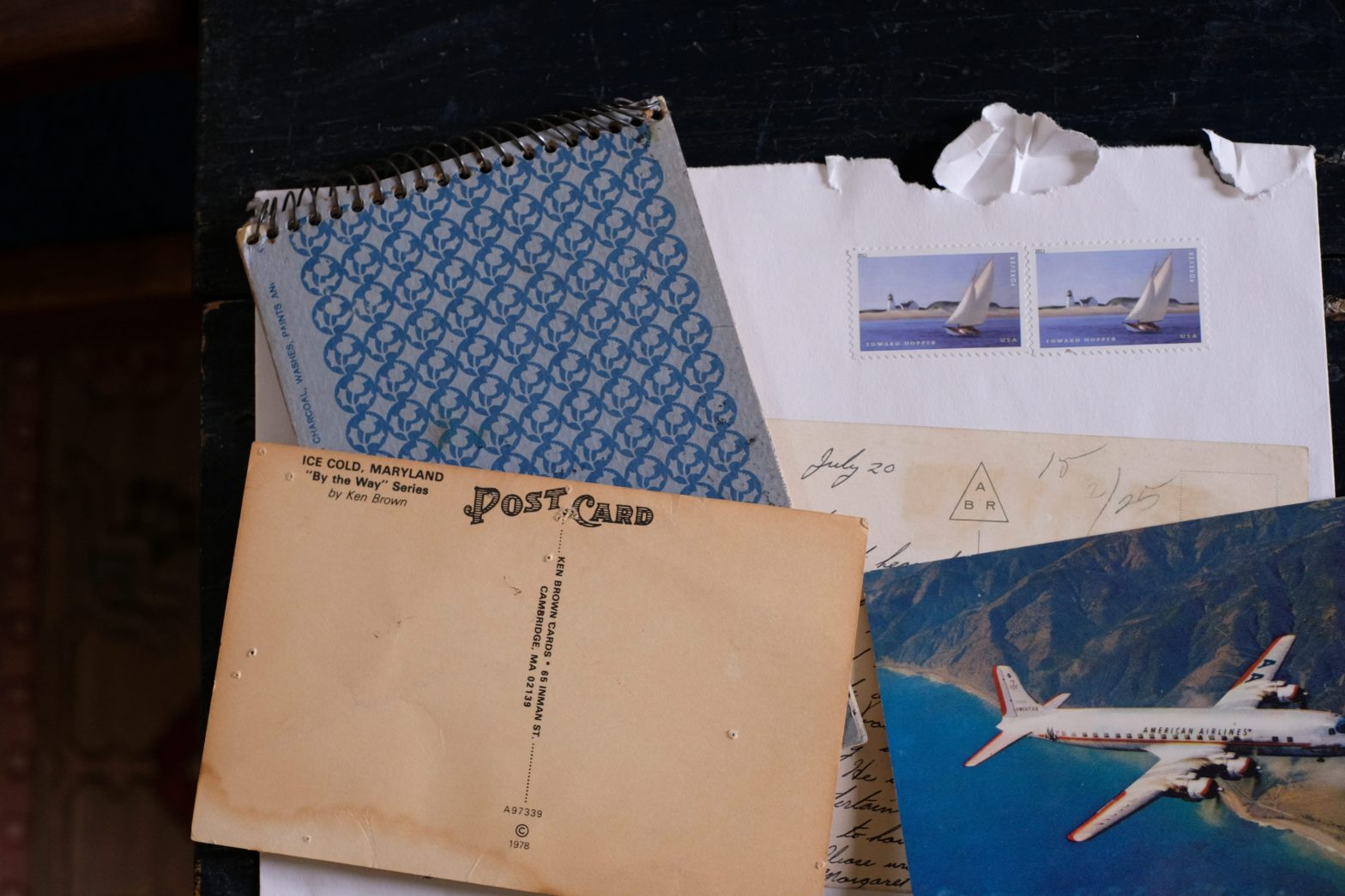 aerial view of a stack of vintage postcards, small notebook, and letter with two stamps torn corner